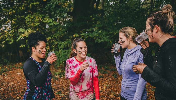 Fun runners covered in mud having a drink