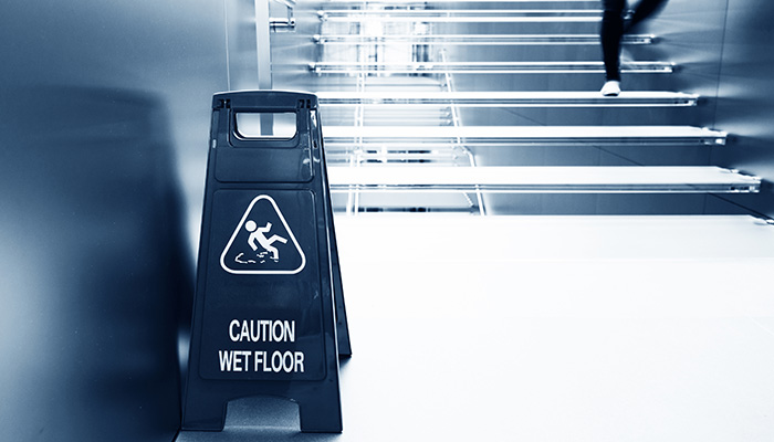 Caution Wet Floor sign at bottom of stairs